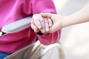senior-lady-in-wheelchair-holding-hands-with-caretaker